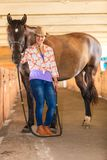 Cowgirl standing next to brown horse friend. Taking care of animals, love and friendship concept. Cowgirl in checkered shirt and cowboy hat leading brown horse royalty free stock photo