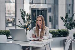 Taking care of business. Beautiful young woman looking at camera and smiling while sitting in the modern restaurant royalty free stock photos