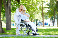 Taking care of patient. Pretty nurse taking care of senior patient in a wheelchair Royalty Free Stock Photos