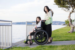 Taking care of sister in wheelchair by beach Stock Images