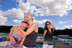 Taking care about you. Three happy young caucasian girlfriends standing together on the yacht dock and having good time together Royalty Free Stock Image