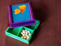 Cut in half pills in the medicine container royalty free stock images