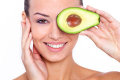 Taking care of your skin the natural way. Beautiful young shirtless woman holding piece of avocado in front of her eye and touching her face while standing Royalty Free Stock Photography