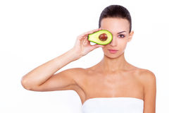 Taking care of your skin the natural way. Studio portrait of a beautiful young woman posing with an avocado over white isolated background Stock Image