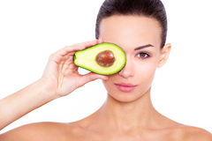 Taking care of your skin the natural way. Studio portrait of a beautiful young woman posing with an avocado over white isolated background Stock Photo
