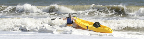 Taking The Challange. Middle aged man with a canoe taking the challange of crossing the rough surf Stock Photo