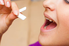 Taking chewing gums. Young woman putting two chewing gum pellets in her mouth Stock Photos
