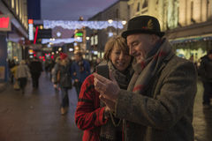 Taking A Christmas City Selfie. Mature couple are in the city centre on an evening at Christmas time. They are using a smart phone to take a selfie together Royalty Free Stock Photo