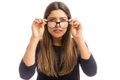 Taking A Closer Look At Things. Young woman with vision problem wearing eyeglasses on white background royalty free stock image