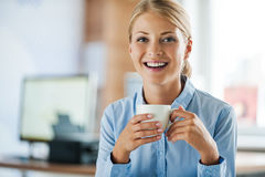 Taking coffee break. Cheerful young businesswoman in formalwear holding cup of coffee and looking at camera while sitting at her working place Royalty Free Stock Images