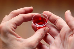 Taking Communion. Hands holding a communion cup filled with wine Royalty Free Stock Images