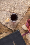 Taking Communion. Cup of glass with red wine, bread and Holy Bible on wooden table close-up Stock Images