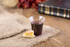 Taking Communion. Cup of glass with red wine, bread and Holy Bible on wooden table close-up. Focus on bread Stock Image
