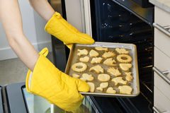 Taking cookies from oven Royalty Free Stock Photo