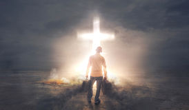 Taking Darkness to the Cross. A man carrying baggages of darkness before a bright glowing cross Stock Image