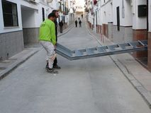 Taking delivery of steel staircase. Alora, Spain - December 15, 2011: Men lifting steel staircase in to village house in Andalusia Royalty Free Stock Photography