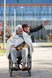Taking disabled man for a walk Stock Photos