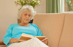 Taking It Easy. Senior lady relaxing with a good book to read Royalty Free Stock Photos