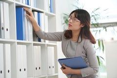 Taking folder. Vietnamese business woman taking binder from the shelf Stock Photography