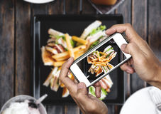 Taking food photo, food photography by smart phone, club sandwich with french fries on wooden table Stock Image