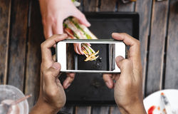 Taking food photo, food photography by smart phone, club sandwich with french fries on wooden table Royalty Free Stock Photography