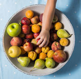 Taking a fruit from a bowl of fruits Royalty Free Stock Photos
