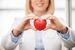 Taking good care of your heart. Close-up of female doctor in white uniform holding heart prop and smiling Stock Photo