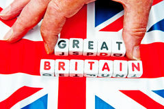 Taking Great out of Great Britain. Text ' Great Britain ' in uppercase letters inscribed on small white cubes placed a Union Jack flag with fingers removing the Stock Photos