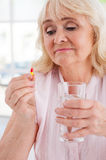Taking her daily medicines. Royalty Free Stock Image