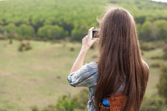 Taking home memories. Young brunette woman using her smart phone to take home memories of hiking stock photos