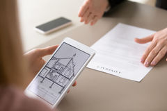 Taking home purchase loan, house plan on screen, close up. Real estate agency clients holding tablet, looking at architectural plan of dream house, considering royalty free stock photo