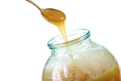 Taking the honey with a spoon from the jar Stock Photos