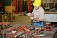 Taking Inventory. Auditor taking inventory of tools in an industrial factory.  Welding equipment is visible in the background Royalty Free Stock Photography