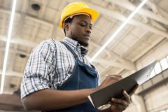 Taking Inventory at Plant Warehouse. Waist-up portrait of concentrated African American technician wearing checked shirt and overall taking necessary notes while Royalty Free Stock Images