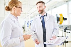 Taking Inventory at Production Department. Bearded middle-aged dairy plant worker and his pretty colleague wearing white coats standing at modern production Royalty Free Stock Photos