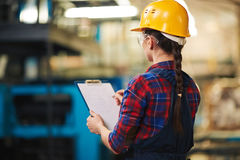 Taking Inventory in Warehouse. Back view of female warehouse worker wearing protective goggles and helmet taking inventory with clipboard, blurred background Stock Photography