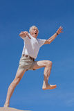 Taking the leap. An mature male in his 60s takes a fearful leap into the blue yonder Stock Images