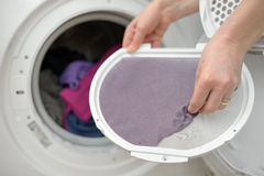 Taking the lent of Dryer Machine. Woman Taking the lent of Dryer Machine Royalty Free Stock Photo