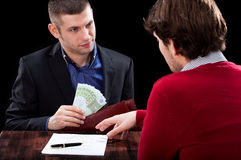 Taking a loan. A men and a banker in the process od giving a cash loan Stock Images