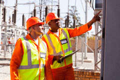 Taking machine readings. Successful electrical engineers taking machine readings in substation Royalty Free Stock Photography