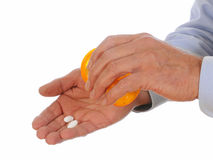 Taking Medication. Dispensing pills from a prescription bottle into his hand set against a white background Royalty Free Stock Photos