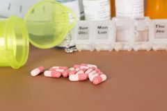Taking medication. Tiny pink pills with medication bottles and containers in background Stock Image