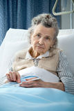Taking the medicine. Senior woman lying at hospital bed and takes the medicine Royalty Free Stock Photos