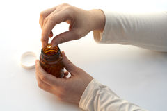 Taking a medicine of the bottle. On white backgraound royalty free stock image