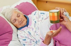Taking the medicine. Elderly woman holding a cup of tea and her medicine Stock Photos