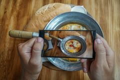 Taking Mobile Photo of Shakshuka Poached Eggs with Tomato and Bread Served in a Frying Pan. Israeli Arab Middle Eastern. Cuisine stock photo