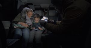 Taking mobile video of mom and kid traveling by minibus and using cell stock video