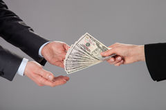 Taking money. Businessman's hands accepting an offer of money on grey background Royalty Free Stock Image