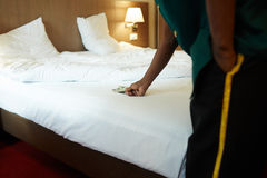 Taking money. Hotel bellman taking tips from bed Royalty Free Stock Photo