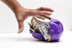 Taking my Savings. A hand taking money from a piggy Stock Images